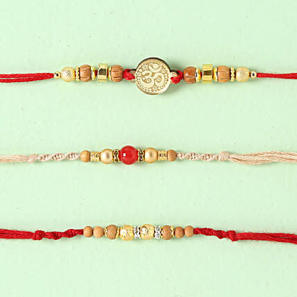 Red Cream Rakhi Set: Set Of 3 Rakhi Delivery in Sweden