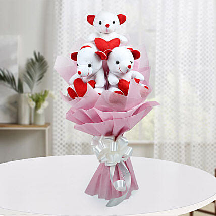 A bouquet of three red and white teddy bears wrapped with pink paper packaging and white ribbon