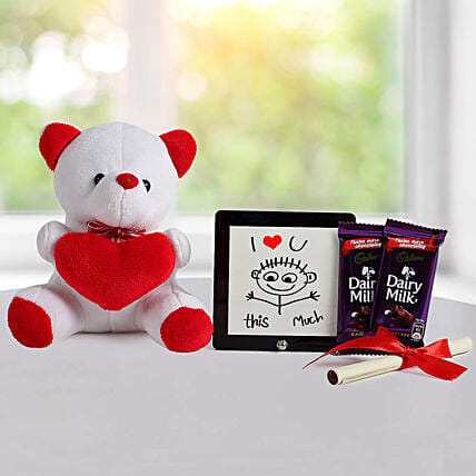 A hamper containing table top, dairy milk , cream teddy bear and a love message gifts:Table tops