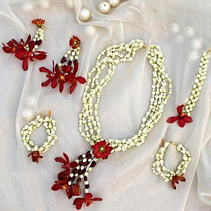 A fresh floral jewelry set of red spider orchids, mogra, red daisies, and white pearls:Flower Jewellery