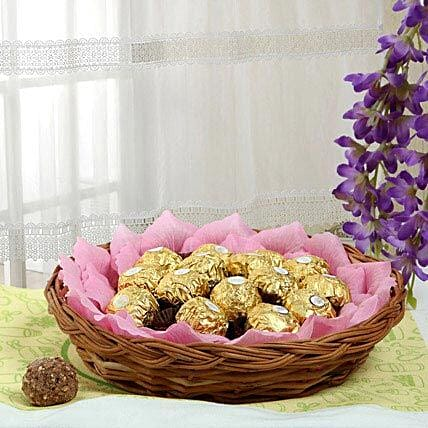 Ferrero rocher chocolates and artificial pink paper petals in a round cane basket:Gift Baskets
