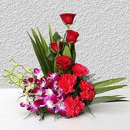 Cane basket arrangement of 4 purple orchids, 4 dark pink carnations, 4 red roses and arica palm leaves flowers