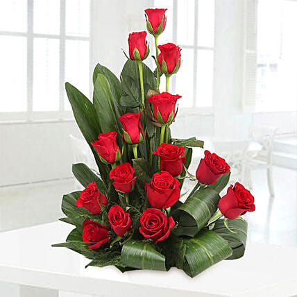 Cane basket arrangement of 15 red roses, draceane leaves and seasonal filler flowers gifts:Send Flowers to Chennai