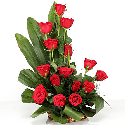 Cane basket arrangement of 15 red roses, draceane leaves and seasonal filler flowers gifts:Happy Birthday Roses