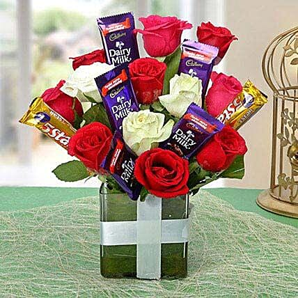Glass vase arrangement of roses and chocolates:Girlfriends Day Chocolates