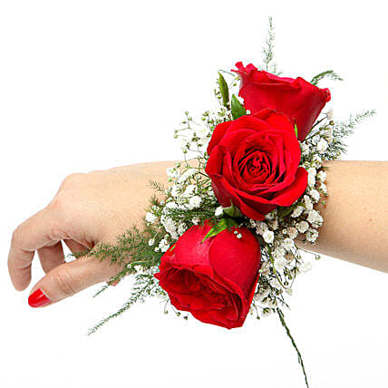 A floral bracelet of red roses and gypsophila