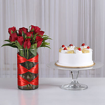 rose bunches in vase with fresh fruit cake