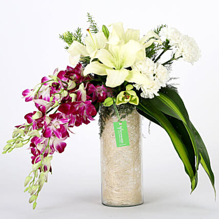 Glass vase arrangement of 6 purple orchids, 3 white asiatic lilies, 6 white carnations with draceane leaves and vase filler flowers gifts:Send Wedding Gifts to Gwalior