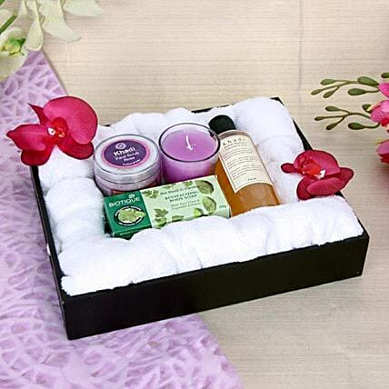 Spa essentials of towel, candle, body soap, face scrub, shampoo and black tray
