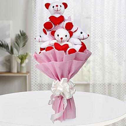 A bouquet of five red and white teddy bears wrapped with pink paper packaging and white ribbon
