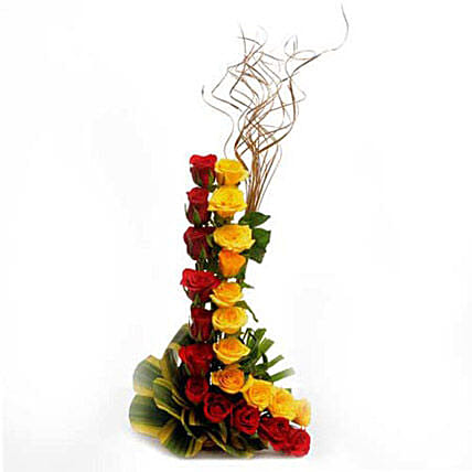Charming Bloom - Basket arrangement of 22 Red and Yellow roses and dry sticks.