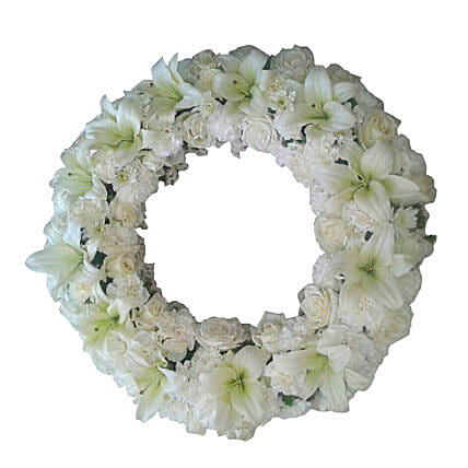 A fresh flower wreath with white roses, white carnations and white asiatic lilies