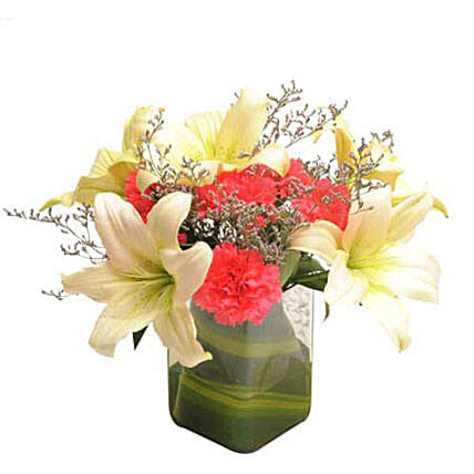 Glass vase arrangement of 6 dark pink carnations, 2 white asiatic lilies, seasonal filler and draceane leaves:Republic Day Flowers Delivery
