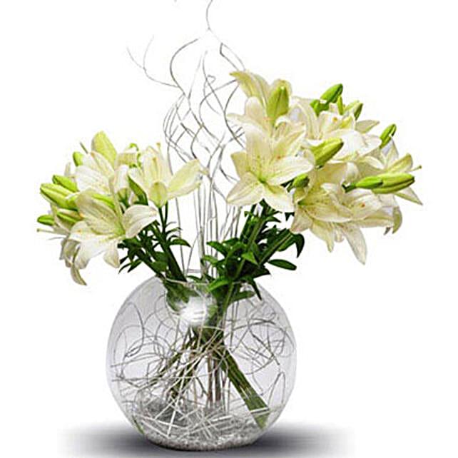 Lily celebration - A glass vase arrangement of a dozen white Asiatic lilies.