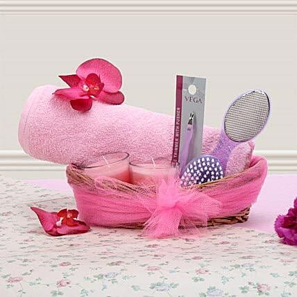 Gift hamper of pink towel, pink glass candle, pedicure tool, manicure tool and cane basket