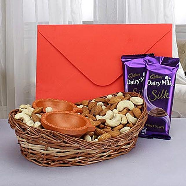 Dry fruits with diyas, greeting card and chocolates